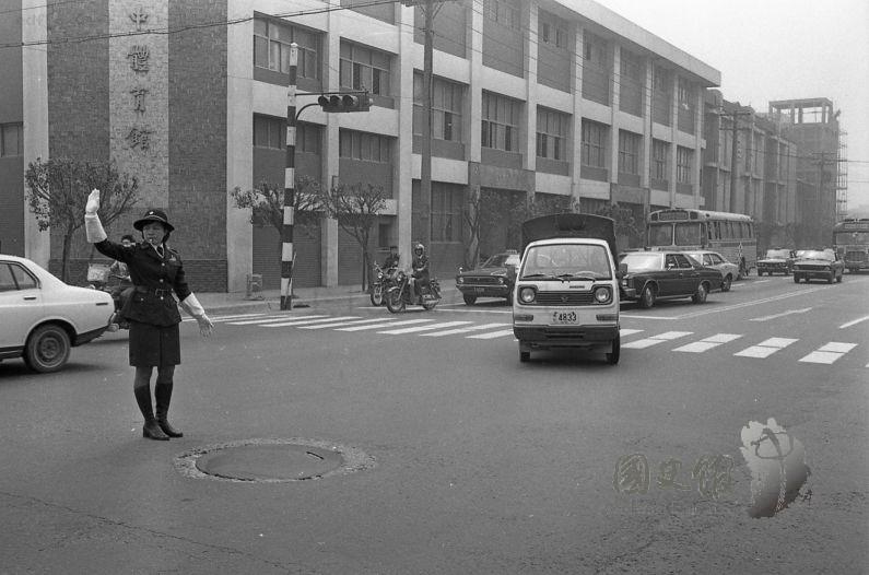 女警們在林森南路與青島東路交叉口接受勤務訓練指揮交通,背景有成功高中體育館。(臺灣新生報66.3.23照片,國史館館藏)
