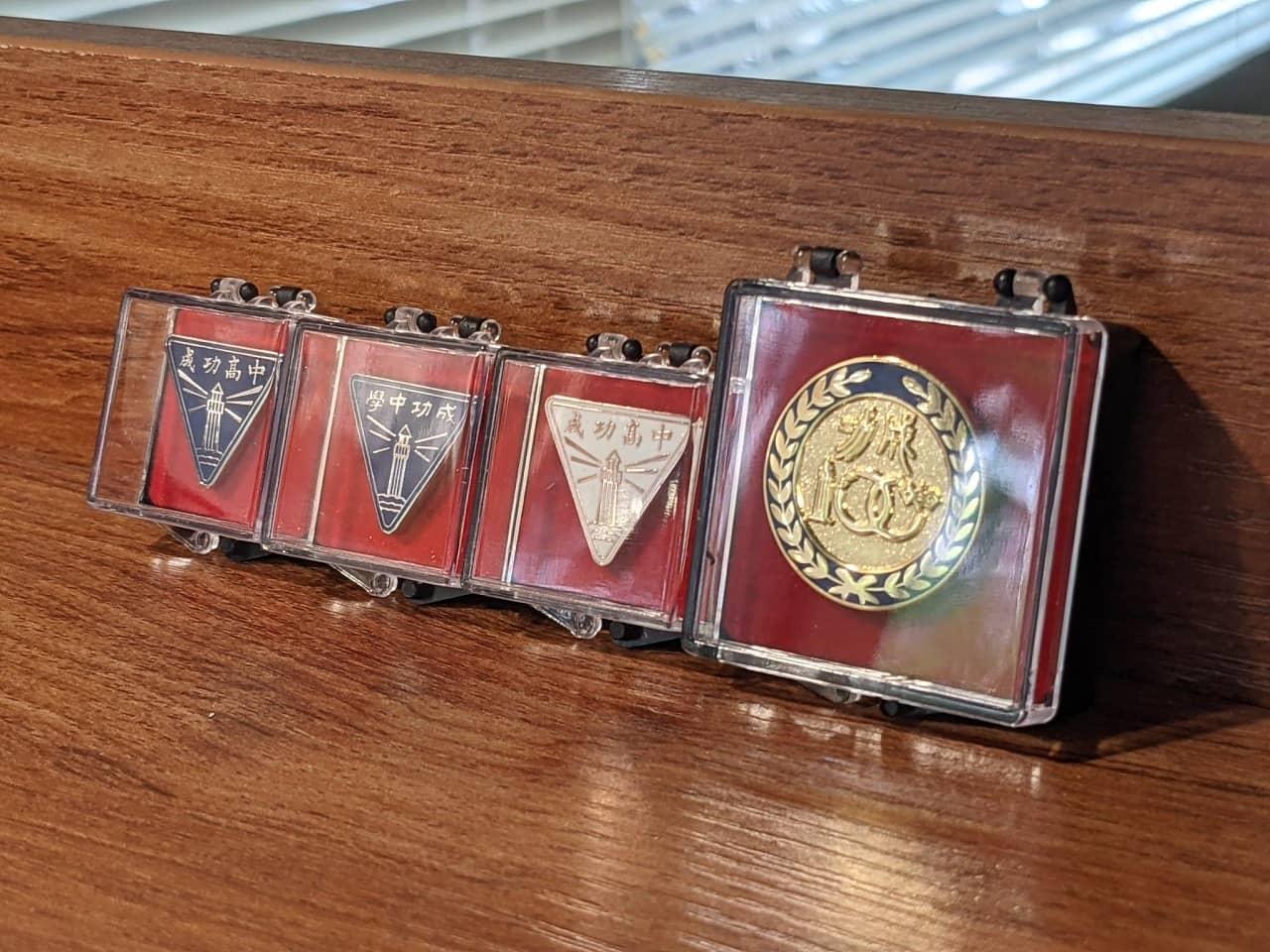 由左至右:成功高中現役校徽、成功中學時期校徽、成功高中現役校徽(玫瑰金特別版)、百週年校慶紀念章。
